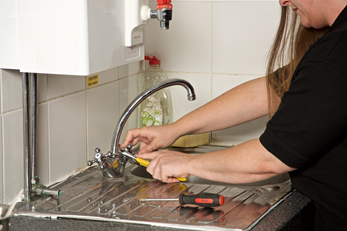 female plumber working on a kitchen tap